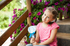 Cute little girl holding white and blue lollipop Stock Images