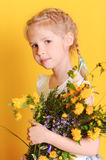 Cute little girl holding yellow flowers. Portrait of cute smiling girl holding bouquet of flowers on yellow background Royalty Free Stock Image