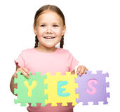 Cute little girl is holding Yes slogan Royalty Free Stock Photo