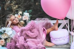 Cute little girl holds French Macaron. Confectionery concept. Of big macarons. Holiday or birthday party for your children royalty free stock images