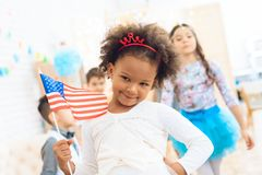 Cute little girl holds a gift and a flag of the USA at the celebration of her birthday. Festive mood concept. Concept of children`s holiday Stock Image