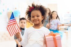 Cute little girl holds a gift and a flag of the USA at the celebration of her birthday. Festive mood concept. Concept of children`s holiday Stock Photo