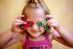 Cute little girl holds two fidget spinners stock photos