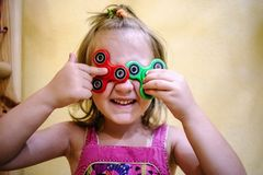 Little girl holds two fidget spinners on her face Royalty Free Stock Photography