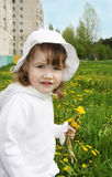 Cute little girl holds yellow dandelions Royalty Free Stock Photography