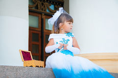 Cute little girl in a holiday white and blue dress is sitting on the steps near the columns Stock Images