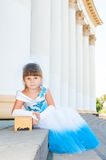 Cute little girl in a holiday white and blue dress is sitting on the steps near the columns Stock Photography