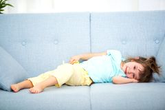 Cute little girl in home clothes lies in the room on the couch.  stock image