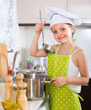 Cute little girl at home kitchen. Happy smiling  little girl cooking alone at home kitchen Royalty Free Stock Images