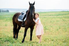 Cute little girl on a horse in a summer field dress. sunny day stock images