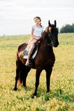 Cute little girl on a horse in a summer field dress. sunny day stock image