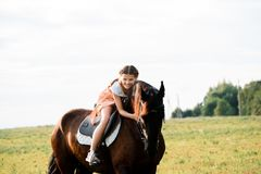Cute little girl on a horse in a summer field dress. sunny day royalty free stock photo