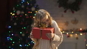 Cute little girl hugging Christmas present near sparkling decorations, dreams. Stock footage stock video