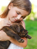Cute little girl hugging her dog puppy. Stock Photography