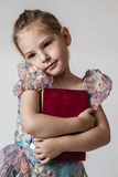 Cute Little Girl Hugging Red Book Stock Image