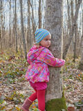 Cute little girl hugging a tree trunk in the spring forest. Royalty Free Stock Images