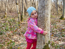 Cute little girl hugging a tree trunk in the spring forest. Stock Photo