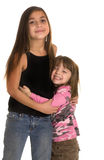 Cute little girl hugs older friend. Funny picture of excited little girl embracing her older friend stock image
