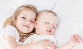 Cute little girl hugs a sleeping baby brother. On a white background Royalty Free Stock Photography