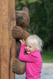 Cute little girl hugs wooden bear Royalty Free Stock Image