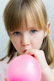 Cute little  girl inflating a pink balloon in the kitchen Stock Images