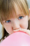 Cute little  girl inflating a pink balloon in the kitchen Stock Photos