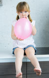 Cute little  girl inflating a pink balloon in the kitchen Royalty Free Stock Photo