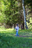 Cute little girl in jeans walking in woods Royalty Free Stock Image
