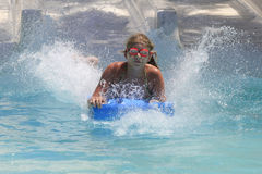 The cute little girl joying  in the water park Stock Photos