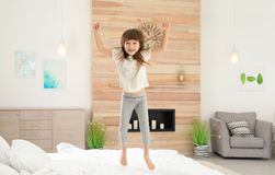 Cute little girl jumping on bed. At home royalty free stock photos