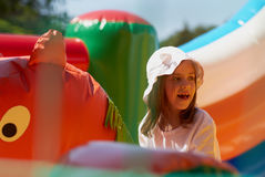 Cute little girl in a jumping castle. Pretty young girl posing in a bouncing castle in a bright sunny day with beautiful smile Royalty Free Stock Image