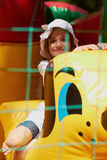 Cute little girl in a jumping castle. Pretty young girl posing in a bouncing castle in a bright sunny day with beautiful smile Stock Photo
