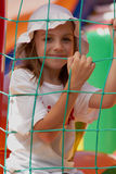 Cute little girl in a jumping castle. Pretty young girl posing in a bouncing castle in a bright sunny day with beautiful smile Stock Image