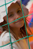 Cute little girl in a jumping castle. Pretty young girl posing in a bouncing castle in a bright sunny day with beautiful smile Royalty Free Stock Photography