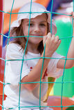 Cute little girl in a jumping castle. Pretty young girl posing in a bouncing castle in a bright sunny day with beautiful smile Royalty Free Stock Photo