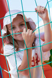 Cute little girl in a jumping castle. Pretty young girl posing in a bouncing castle in a bright sunny day with beautiful smile Royalty Free Stock Photos