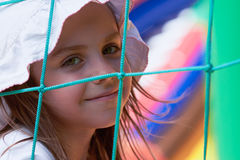 Cute little girl in a jumping castle. Pretty young girl posing in a bouncing castle in a bright sunny day with beautiful smile Stock Images
