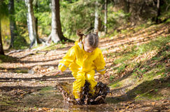 Cute little girl jumping in muddy puddle Royalty Free Stock Photography