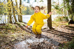 Cute little girl jumping in muddy puddle. Wearing yellow rubber overalls. Happy childhood. Sunny autumn forest stock photography
