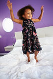 Cute Little Girl Jumping On Parent's Bed Stock Images