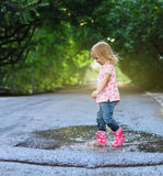 Cute little girl jumping into a puddle Royalty Free Stock Photo