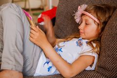 Cute girl kid using iPad digital computer tablet on bed for education or playing game. stock image
