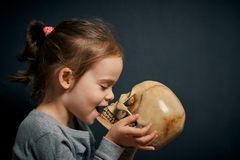 Cute little girl kisses the skull. On a black background stock photography