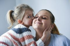 Cute little girl kissing her mother stock photos