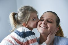 Cute little girl kissing her mother stock photo