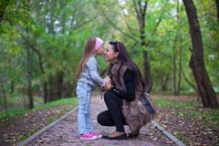Cute little girl kissing her mother's nose Stock Image