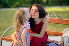 Cute Little Girl is Kissing Her Mother Sitting on the Bench in the City Park. Young Woman Wearing Eyesglasses and Red royalty free stock photography