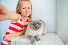 Cute little girl kissing her pet cat at home. Love between kid and pet. Adorable little girl with her pet cat at home. Love between kid and pet Stock Image