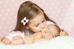 Cute little girl kissing her sleeping newborn sister Stock Photography