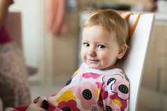 Cute little girl in the kitchen sitting on chair, smiling Royalty Free Stock Images